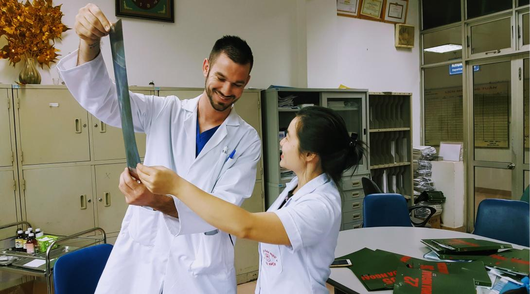 En läkare som åkt som professionell volontär utomlands, tittar på röntgenbilder tillsammans med en lokal läkare.